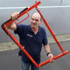Larry Burns shows the device he has designed to stop floodwater getting through doorways. Photo:...