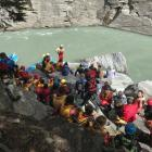 Friends, family and colleagues gather on the bank of the Shotover River on Sunday. PICTURES:...