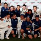 The Black Caps celebrate with the trophy after drawing the second test to secure a series victory...