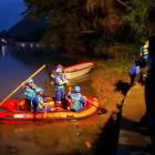 Rescue workers search for people after two dragon boats practicing to race on a river overturned,...