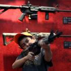 A young attendee inspects an assault rifle. Photo Getty Images