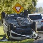 A car lies upside down after a crash on Dukes Rd, Mosgiel,  near the intersection with Factory Rd...