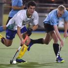 Kings United's Zac White (left) looks to make a pass as University's Maxwell Rasmussen comes...