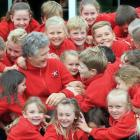 Five Forks School principal Cate Bole (65) is mobbed by pupils yesterday. Today she is retiring...