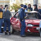 A group stands round a damaged car in Hyde St, Dunedin. Photo: Peter McIntosh