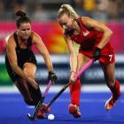 Black Sticks defender Ella Gunson (left) battles for the ball with England midfielder Hannah...