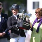 Jonelle Price poses with the trophy flanked by by HRH Princess Anne (L) and Classic Moet's co...