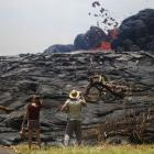 People watch as lava erupts from a Kilauea volcano fissure in Leilani Estates, on Hawaii's Big...