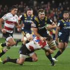 Highlanders No8 Luke Whitelock is tackled by Lions halfback Nic Groom in their Super Rugby match...