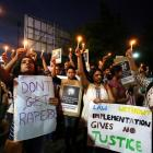 People hold candles and placards during a protest against the rape of an eight-year-old girl and...