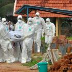 Doctors and relatives wearing protective gear carry the body of a victim, who lost his battle...