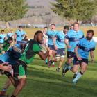 Alexandra player Isimeli Cakautimi carries the ball with determination against Wakatipu players...
