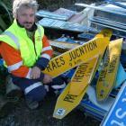 Tapanui auction organiser Brendon Stuart holds the misspelt Raes Junction sign which sold for ...