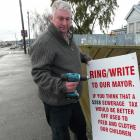 Balclutha pensioner Bruce Graham takes down his protest sign in Clyde St yesterday, after...
