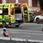 Emergency services attend to a cyclist who was hit by a car yesterday morning. PHOTO: STEPHEN...