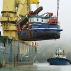 Port Otago's new 650-tonne backhoe dredge Takutai is manoeuvred off the heavy-lift vessel...