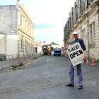Harbour Street Bakery owner Ed Balsink carries a sign for the Tyne St entrance of Harbour St to...