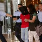 A female suspect is arrested by police officers after a woman opened fire and wounded four people...