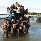 As many East Otago High School pupils as possible squeeze on to one of the Moeraki Boulders...
