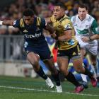 Waisake Naholo is tackled by Ben Lam during the match between the Highlanders and the Hurricanes at Forsyth Barr Stadium 01/06/18. Photo: Getty Images