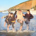 Deane Davison (71), trying the Friendly Bay water with her grandchildren, Eden (10), left,...
