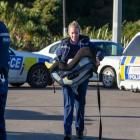 A police officer carries the baby in a car seat after rescuing it from a car involved in the...