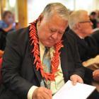 Samoan Prime Minister Susuga Tuilaepa Sailele Malielegaoi signs a copy of his memoir Palemia at...