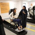 A driving instructor (R) explains seat bells to trainees Amira Abdulgader and Maria Al-Faraj (C)...