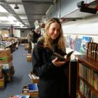 Star Regent 24-Hour Book Sale volunteer Lily Margreiter, of Austria, looks over some books in...
