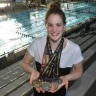 Caitlin Deans (18) at Moana Pool yesterday, holds the six medals she won at the Oceania...