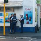 Police talk to a woman outside the Dundas Corner Dairy in North Dunedin yesterday afternoon...