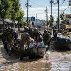Soldiers ferry elderly people to safety following heavy flooding in Kurashiki near Okayama, Japan...