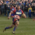 Harbour prop Giorgio Bower breaks through the Taieri defence to score a decisive try gives chase,...