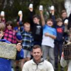 Waitahuna School pupils Tyler Alderton and Issy Young (both 9), with local apiarist Dana Young...