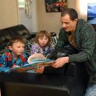 Parent Brendan Selwood reads to his children Alex (6) and Emily (8) at their Brighton home, in...