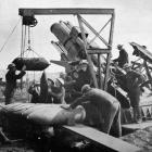 Gunners manhandle shells for one of the huge guns used against the Germans during their recent...