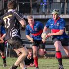 Owaka player Reuben Crossan takes the ball up with support from Chris Chittock (centre left) and...