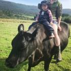 Emma Sutherland and son Henry take a ride on pet cow Rosie. PHOTO: SUPPLIED