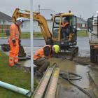 Contractors work on a burst water main at the intersection of High and Green Sts in Mosgiel...