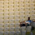 A spectator sits among empty seats as he waits for the start of the final session on the first...