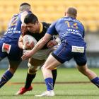 Wellington flanker Du'Plessis Kirifi is tackled by Tomkinson (left) and centre Matt Faddes during...