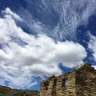 Bright sun shines on this old gold miner's cottage at Bendigo, while puffy cumulus and very high...