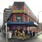 Firefighters, hotel guests and staff wait outside the Leviathan Hotel in central Dunedin after...