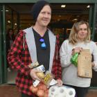 Riley Cooper and Rosie Stamm, of Dunedin, carry their shopping outside Countdown yesterday. PHOTO...