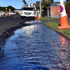 Water flows down Auld St, Dunedin, after a water main was damaged yesterday. Photo: Peter McIntosh