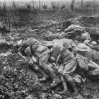 Exhausted stretcher bearers and dressers on a Western Front battlefield fall asleep in the mud,...