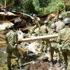 Members of the Japan Self-Defense Forces search for survivors in a house in Atsuma town that was...