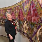 Toitu Otago Settlers Museum visitor host Cora Woodhouse admires embroidered panels highlighting...