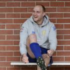 Otago centre Matt Faddes puts his boots on in preparation for training at Logan Park yesterday....