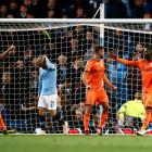 Lyon players celebrate as Manchester City's David Silva is disappointed at his team's loss. Photo...